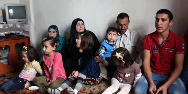 In this Thursday, Nov. 20, 2014 photo, Ahmad Aloun, 19, right, speaks during an interview with The Associated Press as he sits with his family at their house in the northern port city of Tripoli, Lebanon. The Alouns are one of several Syrian families who were given asylum in Uruguay after its government offered to accept 120 refugees. It's a small number compared to the 3 million Syrians who have fled the conflict, now in its fourth year, crowded into overwhelmed neighboring countries or who tri