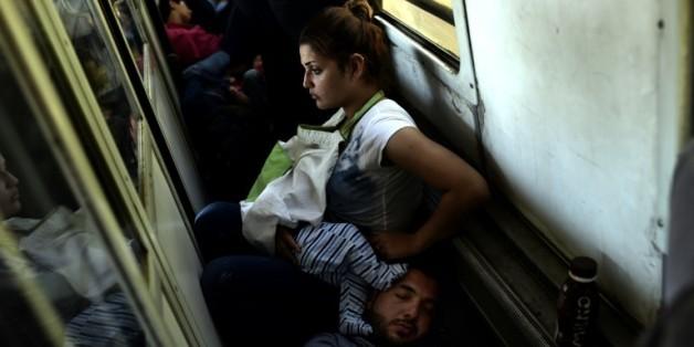 Des réfugiés irakiens Ahmad, Alia et leur bébé Adam voyagent, le 30 août 2015 dans un train de la Macédoine à la Serbie, dans le cadre de leur périple pour rejoindre l'Allemagne