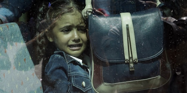 A girl cries as she waits on a bus which will transport her family to the metro station, after their arrival from the northeastern Greek island of Lesbos to the Athens' port of Piraeus on Tuesday, Sept. 8, 2015. About 2,500 refugees and migrants arrived with the ferry Eleftherios Venizelos as Frontex, the EU border agency, says more than 340,000 asylum seekers have entered the 28-nation bloc this year, the majority fleeing war and human rights abuses in Syria, Afghanistan, Iraq, Somalia and Eritrea. (AP Photo/Thanassis Stavrakis)