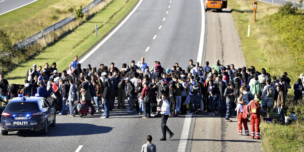 A group of refugees and migrants who were walking north stand on the highway in southern Denmark on Wednesday, Sept. 9, 2015.  The migrants have crossed the border from Germany, and after staying at a local school, they say they are now making their way to Sweden, to seek asylum. (Ernst van Norde/Polfoto via AP) DENMARK OUT
