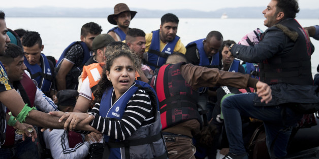 Syrian refugees arrive on a dinghy after crossing from Turkey to Lesbos island, Greece, Wednesday, Sept. 9, 2015. The head of the European Union's executive says 22 of the member states should be forced to accept another 120,000 people in need of international protection who have come toward the continent at high risk through Greece, Italy and Hungary. (AP Photo/Petros Giannakouris)