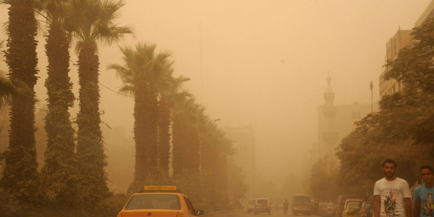 In this photo released by the Syrian official news agency SANA, Syrian citizens cross a street, as a sandstorm shrouds Damascus, Syria, Tuesday, Sept. 8, 2015. The unseasonal sandstorm hit Lebanon and Syria, reducing visibility and sending dozens to hospitals with breathing difficulties because of the fine dust. (SANA via AP)