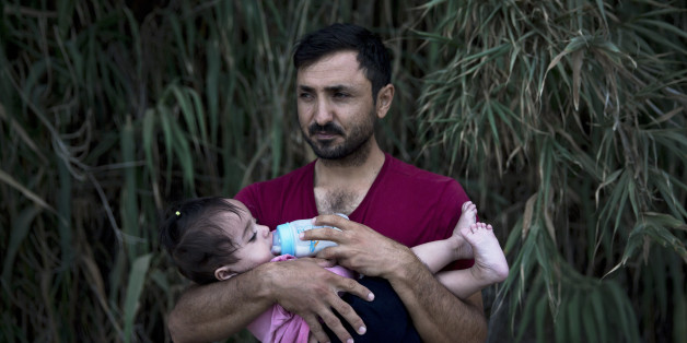 A Syrian refugee feeds milk to his daughter after they arrived on a dinghy, from Turkey to Lesbos island, Greece, Wednesday, Sept. 9, 2015. The head of the European Union's executive says 22 of the member states should be forced to accept another 120,000 people in need of international protection who have come toward the continent at high risk through Greece, Italy and Hungary. (AP Photo/Petros Giannakouris)