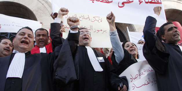 "Tunisian magistrates and lawyers demonstrate as they ask for independence of the Judiciary system in Tunis, Tunisia, Saturday Feb. 12, 2011. The  banner reads : ""Down to the corruption within magistrates"". (AP Photo/Hassene Dridi)"