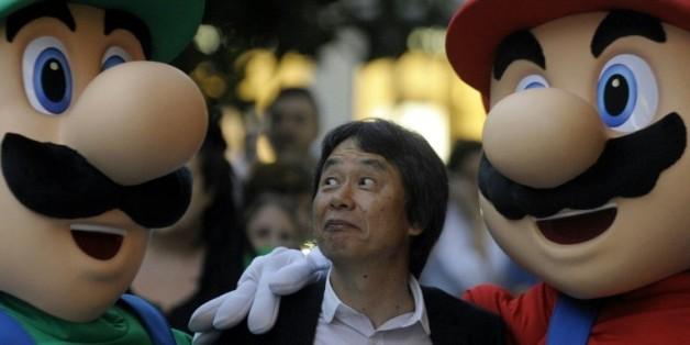 """Le créateur de jeux vidéo japonais Shigeru Miyamoto (C), pose avec le célèbre """"Super Mario"""" (D) et son frère Luigi (G), le 25 octobre 2012 à Gijon (Espagne)"""