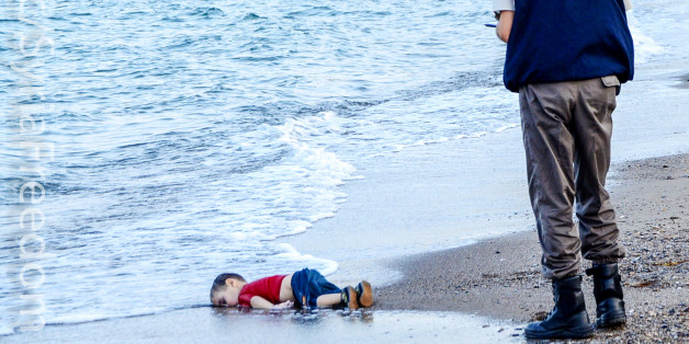 GRAPHIC CONTENTA Turkish police officer stands next to a migrant child's dead body off the shores in Bodrum, southern Turkey, on September 2, 2015 after a boat carrying refugees sank while reaching the Greek island of Kos. Thousands of refugees and migrants arrived in Athens on September 2, as Greek ministers held talks on the crisis, with Europe struggling to cope with the huge influx fleeing war and repression in the Middle East and Africa. AFP PHOTO / Nilufer Demir / DOGAN NEWS AGENCY