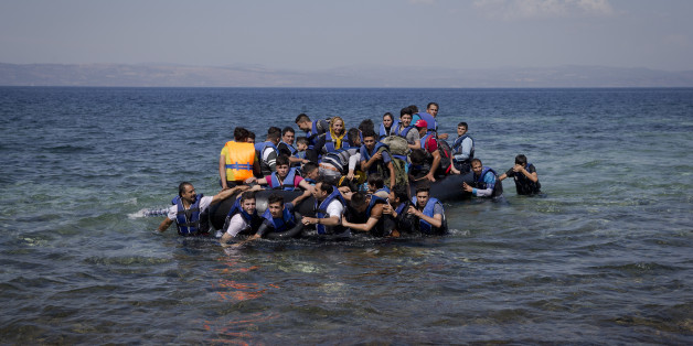 Refugees and migrants arrive on a dinghy after crossing from Turkey to Lesbos island, Greece, Friday, Sept. 11, 2015. While migrants for years have taken death-defying trips across the Mediterranean to reach the relative peace and comfort of the Europe Union, the flow has hit record proportions this year _ notably with an influx of Syrians, Afghans and Eritreans fleeing trouble back home.(AP Photo/Petros Giannakouris)