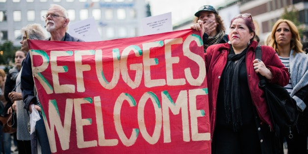 People hold a banner 'refugees welcome' as they take part in a demonstration in solidarity with refugees seeking asylum in Europe after fleeing their home countries in Stockholm on September 12, 2015. AFP PHOTO/JONATHAN NACKSTRAND        (Photo credit should read JONATHAN NACKSTRAND/AFP/Getty Images)