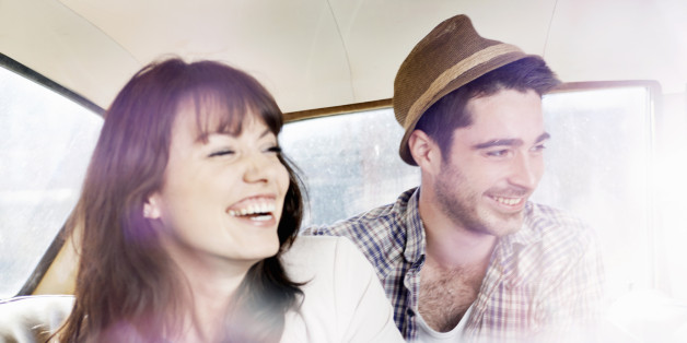 man and woman laughing in car