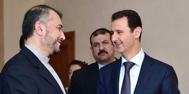 """In this photo released on the official Facebook page of the Syrian Presidency, Syrian President Bashar Assad, right, speaks with Iran's Deputy Foreign Minister Hossein Amir Abdollahian, left, in Damascus, Syria, Thursday, Sept. 3, 2015. Abdollahian says Syrian President Bashar Assad has a """"pivotal and central"""" role to play in the war on terrorism and is an important part of any solution for the war-torn country. (Syrian Presidency via Facebook)"""