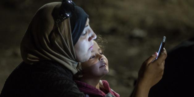 헝가리 국경지대 로즈케에서 한 소녀가 엄마의 휴대폰 화면을 들여다보고 있다.