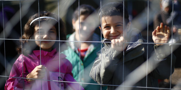 Children smile into the camera behind a fence in a temporary holding center for migrants near the border line between Serbia and Hungary in Roszke, southern Hungary in Roszke, Saturday, Sept. 12, 2015. Hundreds of thousands of Syrian refugees and others are still making their way slowly across Europe, seeking shelter where they can, taking a bus or a train where one is available, walking where it isn't. The latest string of walkers made their way Friday from the Hungarian border across Austria t
