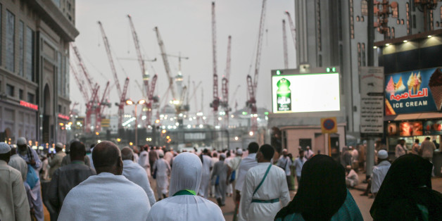 Muslim pilgrims walk towards the Grand Mosque in the holy city of Mecca, Saudi Arabia, marked by towering cranes used in the ongoing expansion aimed to accommodate the growing numbers of annual pilgrims, Sunday, Sept. 13, 2015. A towering construction crane toppled over on Friday during a violent rainstorm in the Saudi city of Mecca, Islam's holiest site, crashing into the Grand Mosque and killing over a hundred people, ahead of the start of the annual hajj pilgrimage later this month. (AP Photo