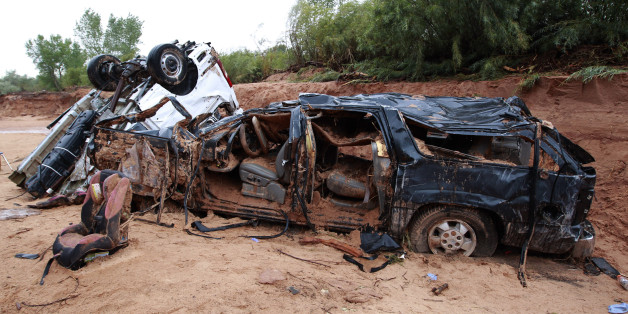 HILDALE, UT - SEPTEMBER 15: The twisted wreckage  of two vans that were washed away in a flash flood with women and children inside rest on the bank of Short Creek on September 15, 2015 in Hildale, Utah. Flash Floods from heavy rains on  the afternoon of September 14, 2015 washed away two vans in Hildale as they were crossing a flooded creek, killing 12 people with one still missing. (Photo by George Frey/Getty Images)