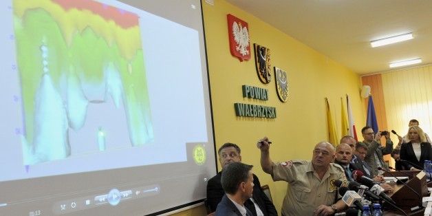 The discoverer Krzysztof Szpakowski (3rdL) presents the georadar picture of a tunnel during a press conference concerning the discovery of a new tunnel, part of an underground structures of unknown purpose built in Owl Mountains during the WWII by Nazi Germany, on September 11, 2015 in Walbrzych. The tunnel is supposed to lead from railway station, near the cemetery and towards one part of Riese project - Wlodarz. Rumours of two special Nazi trains disappearing in the spring of 1945, towards the