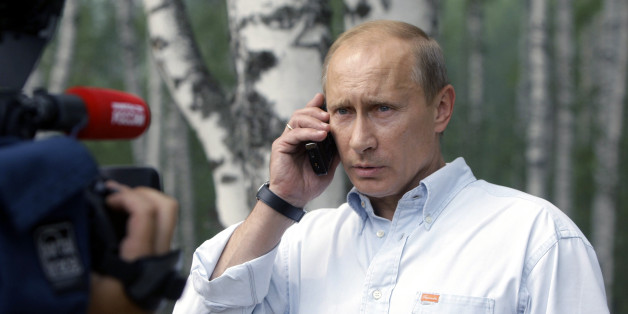 Prime Minister Vladimir Putin speaks on a cell phone with President Dmitry Medvedev, during a visit to a temporary shelter for the people whose houses were burned to the ground in the villages, surrounding Nizhny Novgorod, Russia's fifth-largest city, 475 km (300 miles) east of Moscow, Friday, July 30, 2010. The fires have spread quickly across more than 200,000 acres (90,000 hectares) in recent days after a record heat wave and severe drought that has plagued Russia for weeks.(AP Photo/RIA Novo