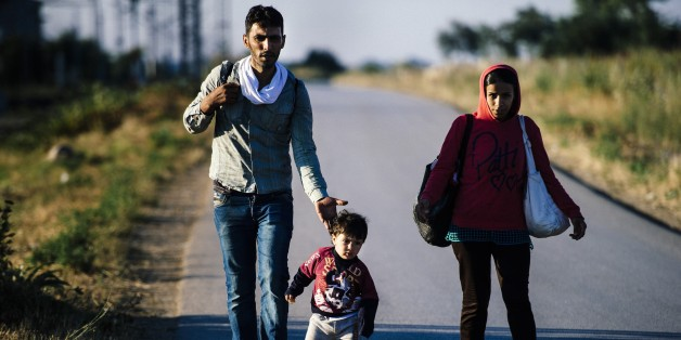 A migrant family walks on a road near the southern Serbian town of Presevo, near the border with Macedonia, on July 15, 2015. Migrants cross Serbia to join other European countries, as it has land borders with three EU countries - Romania, Hungary and Croatia. The estimated number of people crossing the Serbia-Hungary border has increased more than 25-fold, rising from 2,370 to 60,602 according to an Amnesty International report.  AFP PHOTO/DIMITAR DILKOFF        (Photo credit should read DIMITAR DILKOFF/AFP/Getty Images)