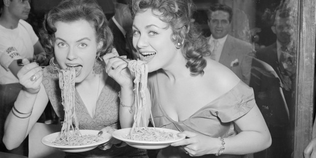 Mirv Arvinen (Miss Finland 1955) and Soho's Fair Queen Andria Loran (right) try their hand at scoffing a plate of pasta at the Soho Fair spaghetti-eating contest on Frith Street, Soho, London.