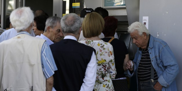 A pensioner waits to enter a bank as others stand in a queue to use an ATM of the branch in Athens, Thursday, July 9, 2015. Greece's government is racing to finalize a plan of reforms for its third bailout, hoping this time the proposal will meet with approval from its European partners and stave off a potentially catastrophic exit from Europe's joint currency, the euro, within days. (AP Photo/Thanassis Stavrakis)