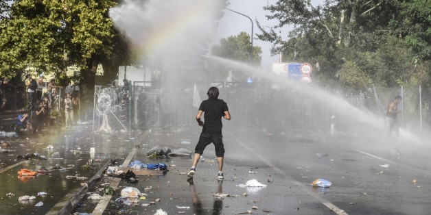 A man stands opposite Hungarian riot police using water cannon to push back refugees at the Hungarian border with Serbia near the town of Horgos on September 16, 2015. Europe's 20-year passport-free Schengen zone appeared to be a risk of crumbling with Germany boosting border controls on parts of its frontier with France as migrants desperate to find a way around Hungary's border fence began crossing into Croatia. With a string of EU countries tightened frontier controls in the face of the unpre