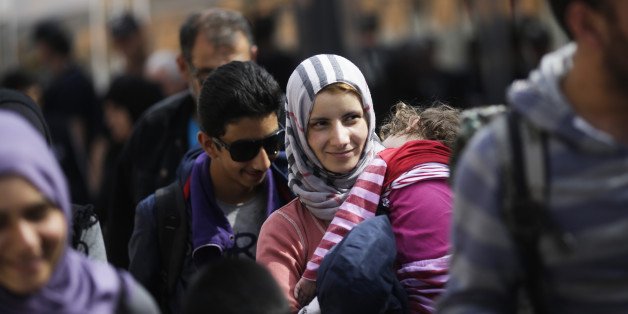 A woman with a baby, saying they are from Syria, arrives with other refugees at the train station of the southern German border town Passau, Tuesday, Sept. 15, 2015, after they have been taken off a train by German border police for registration. Germany introduced temporary border controls Sunday to stem the tide of thousands of refugees streaming across its frontier, sending a clear message to its European partners that it needs more help with an influx that is straining its ability to cope. (AP Photo/Markus Schreiber)