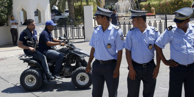 Tunisian police officers guard the Imperial Marhaba hotel during visit of top security officials of Britain, France, Germany and Belgium in Sousse, Tunisia, Monday, June 29, 2015. British Home Secretary Theresa May, French Interior Minister Bernard Cazeneuve, German Interior Minister Thomas de Maiziere and Belgian Interior Minister Jan Jambon joined their Tunisian counterpart on the beach in front of the Imperial Marhaba hotel in the Mediterranean resort of Sousse for the tribute Monday. (AP Photo/Darko Vojinovic)
