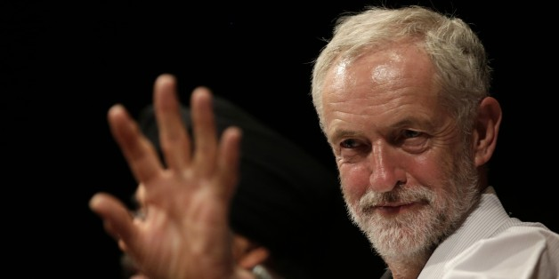 British lawmaker Jeremy Corbyn waves to a member of the audience prior to addressing a meeting during his election campaign for the leadership of the British Labour Party in Ealing, west London, Monday, Aug. 17, 2015. (AP Photo/Alastair Grant)