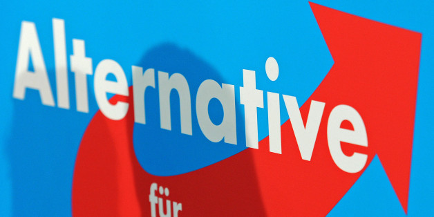 The shadow of top candidate of the Alternative for Germany, AfD, Bernd Lucke falls on the party's logo during a press conference after Germany's general election in Berlin, Monday, Sept. 23, 2013. The  new anti-euro party reached 4.7 percent and will not be in the parliament for the next legislative period. (AP Photo/Jens Meyer)