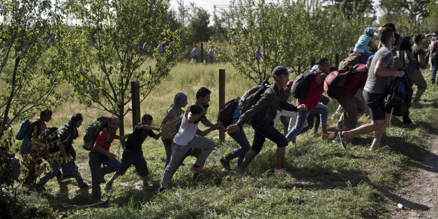 People run amid scuffles with the Croatian police in Tovarnik, Croatia, Thursday, Sept. 17, 2015. Hundreds of migrants have pushed through police lines in the eastern Croatian town of Tovarnik,  with people trampling and falling on each other amid the chaos, as more than 2,000 men, women and children were stuck at the local train station for hours in blazing heat and sun on Thursday, waiting to board trains and buses for transport to refugee centers. (AP Photo/Marko Drobnjakovic)
