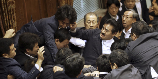 Opposition lawmakers surge toward the chairman's seat to protest as ruling party colleagues rush in to try to protect him during a committee voting of security bills at the upper house in Tokyo, Thursday, Sept. 17, 2015. Japan's ruling Liberal Democratic Party pushed contentious security bills through a legislative committee, catching the opposition by surprise and causing chaos in the chamber. If the vote stands, the legislation will go to the upper house of parliament for final appro
