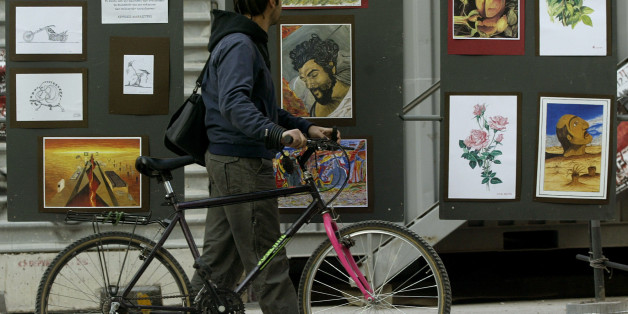 A man wheels his cycle past an exhibition of artwork by convicted November 17 left-wing terrorists, hosted in the grounds of the National Technical University in Athens, Greece, on Tuesday Nov. 15, 2005. The building is the focus of celebrations, starting Tuesday, for the 32nd anniversary of a student uprising that helped bring down the military dictatorship that ruled Greece from 1967-74. Fifteen members of the left-wing group, named after the 1973 uprising, were jailed in 2003 for terrorist activities. The group killed 23 people in a string of attacks between 1975 and 2000. (AP Photo/Petros Giannakouris)