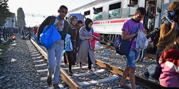 TOVARNIK, CROATIA - SEPTEMBER 18:  People move past a train on the tracks as migrants remain at Tovarnik railway station waiting to leave following crossing from Serbia on September 18, 2015 in Tovarnik, Croatia. Officials are saying that they had no choice than to close eight road border crossings yesterday after more than 11,000 people entered the country since Hungary fenced off its border with Serbia earlier this week.  (Photo by Jeff J Mitchell/Getty Images)