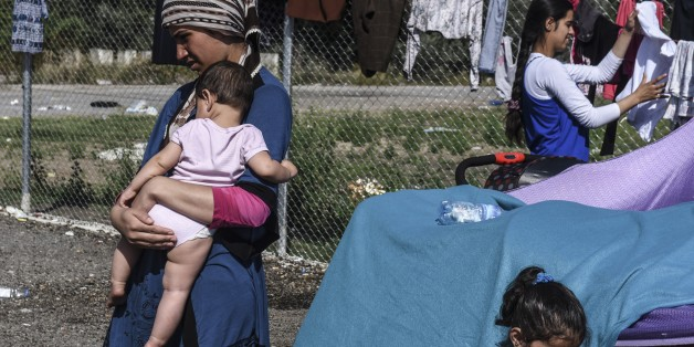 A woman carries her baby at a makeshift refugee camp on the Serbian side of the border with Hungary near the town of Horgos, Sept. 18, 2015. (AFP)