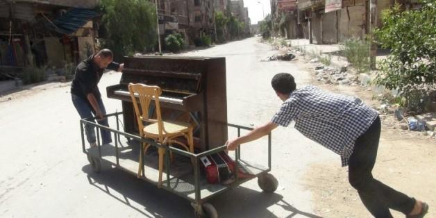 Image du 26 juin 2014 d'Aeham al-Ahmad, poussant son piano à Yarmouk, aux portes de Damas  © AFP/Archives RAMI AL-SAYED