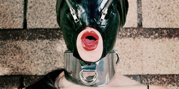 Woman wearing dominatrix outfit with zipper latex mask