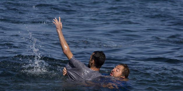 Local resident Dimitris Karapanagiotis, right,  rescues an Afghan migrant whose boat stalled at sea while crossing with others from Turkey to the island of Lesbos, Greece, on Saturday, Sept. 19, 2015. A girl about five years old died and at least 13 undocumented refugees and migrants were missing on Saturday after a boat transferring dozens of people from Turkey to Greece overturned off Lesbos island, Greek Coast Guard said. (AP Photo/Petros Giannakouris)
