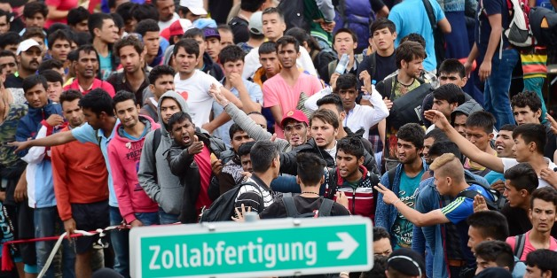 Refugees crowd at the Hungarian-Austrian border in Szentgotthard, Hungary, as thousands of migrants wait for their departure to Germany on September 19, 2015.     AFP PHOTO / ATTILA KISBENEDEK        (Photo credit should read ATTILA KISBENEDEK/AFP/Getty Images)