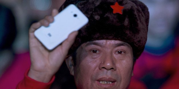 A fan of Xiaomi smartphone holds up one of the phones during a product unveiling event of the Chinese company in Beijing, Thursday, Jan. 15, 2015. The Chinese manufacturer on Thursday unveiled a new model that Lei said has processor size and performance comparable to Apple's iPhone 6 but is thinner and lighter. (AP Photo/Ng Han Guan)
