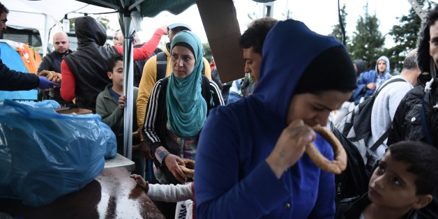 Refugees and migrants queue as police officers hand out milk and bread in the northern Greek village of Idomeni, Monday, Sept. 21, 2015. Hundreds of refugees and economic migrants arrive daily in Idomeni, a small village of some 100 inhabitants, to cross into Macedonia, from where they continue through Serbia and Hungary to seek asylum in wealthier European countries. (AP Photo/Giannis Papanikos)