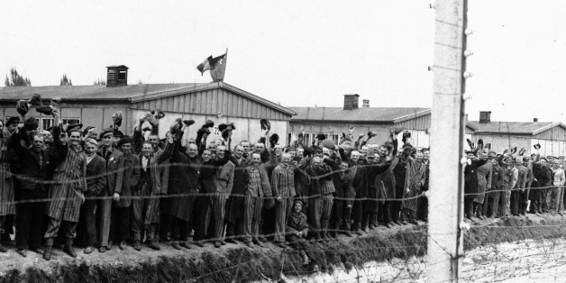 Prisoners at the electric fence of Dachau concentration camp cheer the Americans in Dachau, Germany in an undated photo. Some of them wear the striped blue and white prison garb. They decorated their huts with flags of all nations which they had made secretly as they heard the guns of the 42nd Rainbow Div., getting louder and louder on the approach to Dachau. (AP Photo)