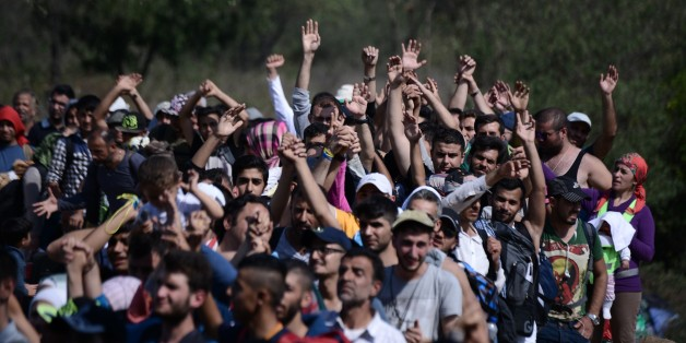 Refugees and migrants raise their hands in order to be allowed by the Macedonian police to cross the border from the northern Greek village of Idomeni to southern Macedonia, Sunday, Sept. 20, 2015. More than 2,000 refugees and economic migrants wait at the small village of about 100 inhabitants every day to be let into Macedonia, from where they continue through Serbia and Hungary to seek asylum in wealthier European countries. (AP Photo/Giannis Papanikos)