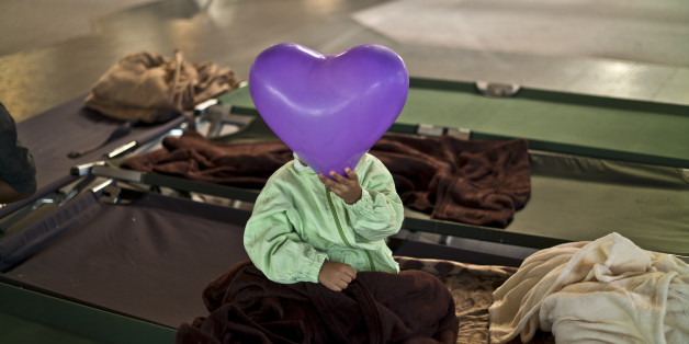 """An Afghan refugee child covers his face with a balloon while he and other migrants spent the night in a shelter near Graz, Austria, Tuesday, Sept. 22, 2015. Hungary's prime minister Viktor Orban said that millions of migrants are """"laying siege"""" to the borders of his country and of Europe, putting the continent in danger.  (AP Photo/Muhammed Muheisen)"""