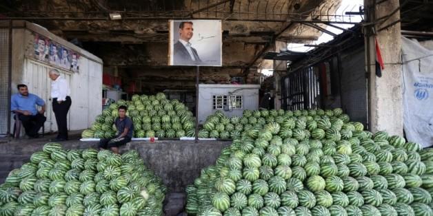 Des négociants syriens près du portrait du président Bachar al-Assad au marché des Halles de Damas, le 21 septembre 2015
