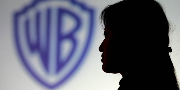 A Chinese woman stands in front of a Warner Home Video logo at a press conference in Beijing Thursday Feb. 24, 2005.  Warner said it will take its battle against rampant piracy of films and music to the front lines and sell cut-rate DVDs in China in a bid to compete on the counterfeiters' home turf. The company will sell basic DVDs, to be available shortly after a film's theatrical release,  in China for as little as 22 yuan (US$2.65). (AP Photo/Greg Baker)