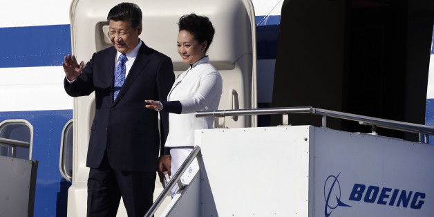Chinese President Xi Jinping, left, and his wife Peng Liyuan wave on their arrival Tuesday, Sept. 22, 2015, at Boeing Field in Everett, Wash. Xi is spending three days in Seattle before traveling to Washington, D.C., for a White House state dinner on Friday. (AP Photo/Elaine Thompson)