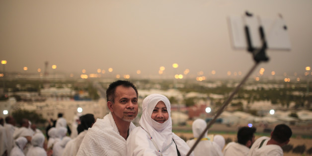 A Muslim pilgrim couple take a selfie on a rocky hill called the Mountain of Mercy, on the Plain of Arafat, near the holy city of Mecca, Saudi Arabia, Tuesday, Sept. 22, 2015. Mount Arafat, marked by a white pillar, is where Islam's Prophet Muhammad is believed to have delivered his last sermon to tens of thousands of followers some 1,400 years ago, calling on Muslims to unite. (AP Photo/Mosa'ab Elshamy)