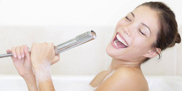 Bath woman singing in bathtub using shower head having fun. Funny photo of cute young mixed race woman.