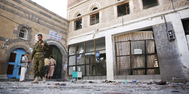 Shiite fighters, known as Houthis, inspect the the scene at the al-Balili mosque after two suicide bombings at the mosque during Eid al-Adha prayers in Sanaa, Yemen, Thursday, Sept. 24, 2015. (AP Photo/Hani Mohammed)