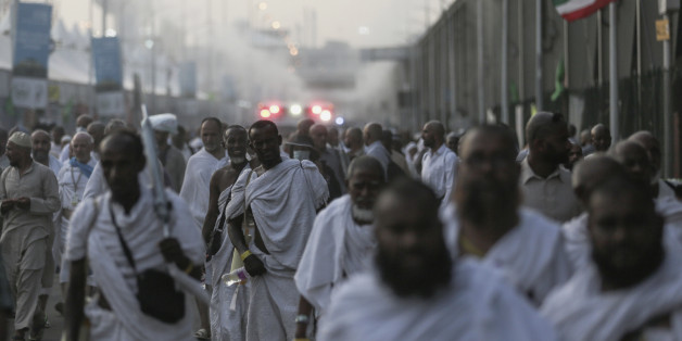 Pilgrims walk by the site where pilgrims were crushed and trampled to death during the annual hajj pilgrimage in Mina, Saudi Arabia, Thursday, Sept. 24, 2015. The crush killed hundreds of pilgrims and injured hundreds more in Mina, a large valley on the outskirts of the holy city of Mecca, the deadliest tragedy to strike the pilgrimage in more than two decades. (AP Photo/Mosa'ab Elshamy)