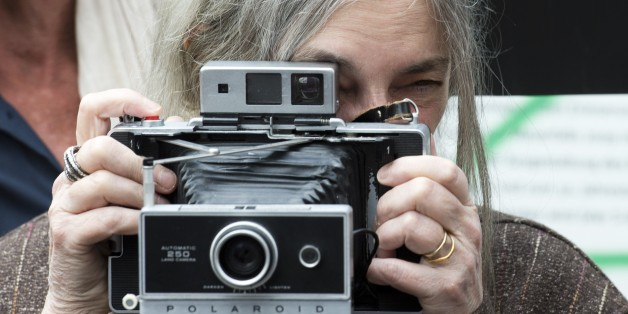 US singer-songwriter Patti Smith poses with her camera in front of a stretch of the Berlin wall on May 21, 2015. Smith and Dercon will present Amnesty International's Ambassador of Conscience Awards 2015 to US singer Joan Baez and Chinese artist Ai Wei-Wei during a ceremony on May 21, 2015 AFP PHOTO / JOHN MACDOUGALL        (Photo credit should read JOHN MACDOUGALL/AFP/Getty Images)